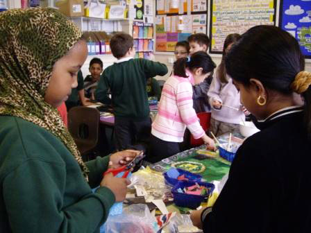 These children are cutting up shiny stickers to add to the border. The collage also had glitter stuck to it.